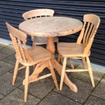 Solid pine tilt top circular table with three pine chairs two of which are matching but the third is slightly different as seen in picture two. £75